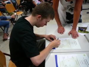 Luuk ondertekent zijn diploma