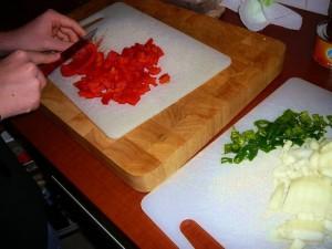 Snipper de ui, maak de paprika en pepers schoon en snijd ze in stukjes